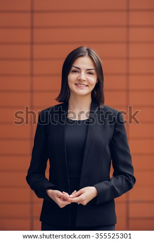 Pretty business women standing in front of orange wall  - stock photo