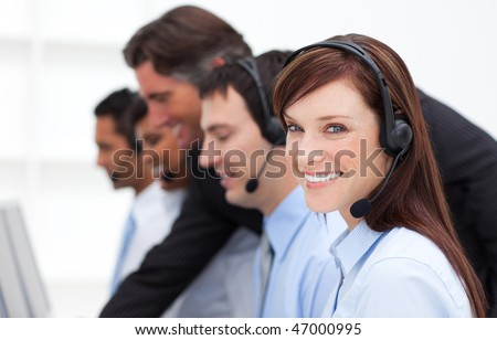 Pretty businesswoman and her team working in a call center in a company - stock photo