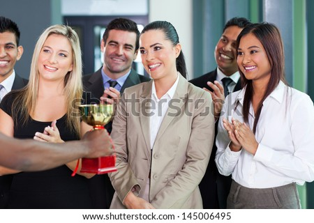 pretty businesswoman and team receiving a trophy - stock photo