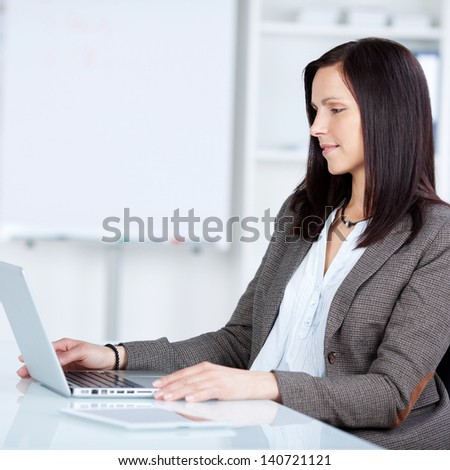 Pretty businesswoman browsing through the laptop in a side view shot