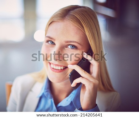 Pretty businesswoman calling on the phone and looking at camera - stock photo