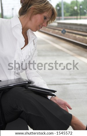 Pretty businesswoman checking her foot which hurts after having walked on high heels all day - stock photo