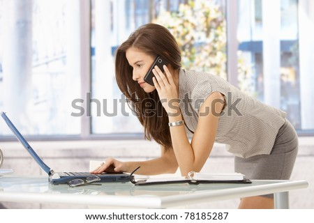 Pretty businesswoman concentrating on multitasking at desk, using laptop computer, talking on mobile phone.?