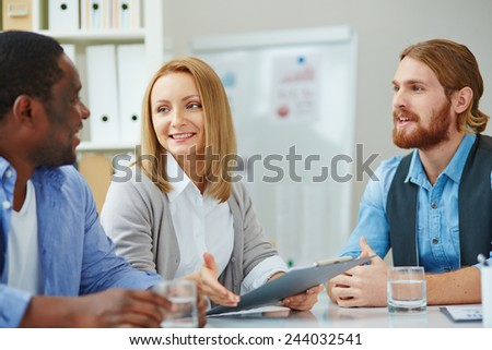 Pretty businesswoman explaining strategy to colleagues at meeting - stock photo