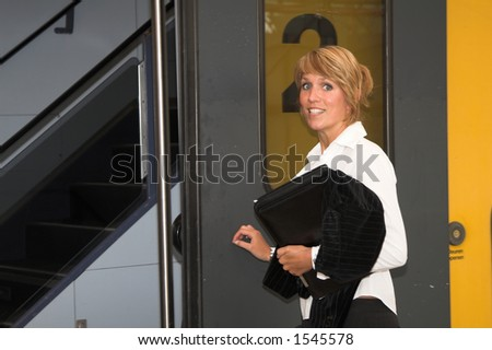 Pretty businesswoman getting on the train - stock photo