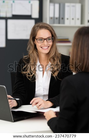 Pretty businesswoman having a discussion in the office with a female colleague, over the shoulder view of the lady in glasses - stock photo
