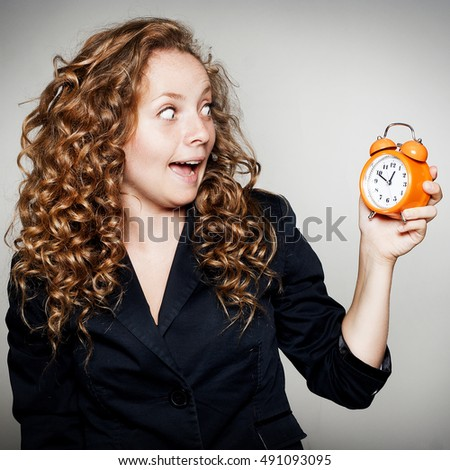 Pretty Businesswoman holding clock in hands. Deadline concept with shocked woman holding alarm clock.