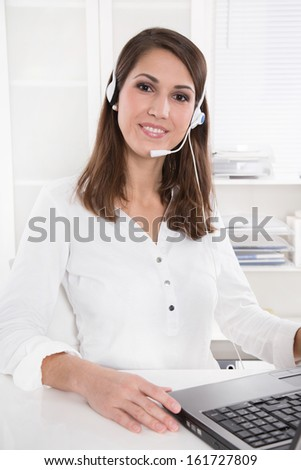 Pretty businesswoman in white sitting at helpdesk and laptop with headset - stock photo