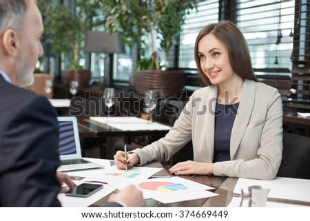 Pretty businesswoman is explaining her ideas about work to her client. She sitting at the table in restaurant and smiling. The woman is working with documents - stock photo