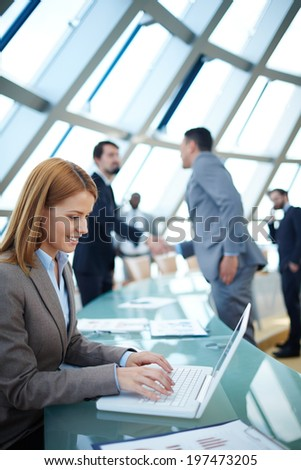 Pretty businesswoman networking or planning work on background of colleagues handshaking - stock photo