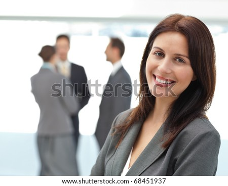 Pretty businesswoman posing in front of her team while working in the background - stock photo