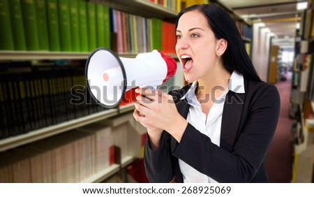 Pretty businesswoman shouting with megaphone against rows of bookshelves in the library - stock photo