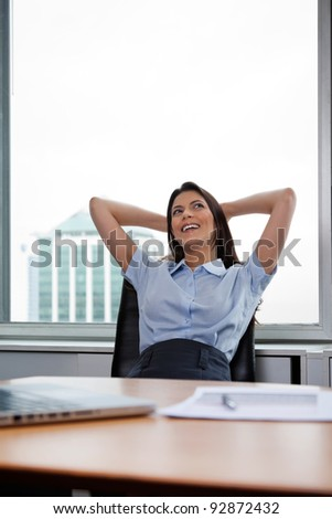 Pretty businesswoman sitting on office chair and relaxing with hands behind head - stock photo