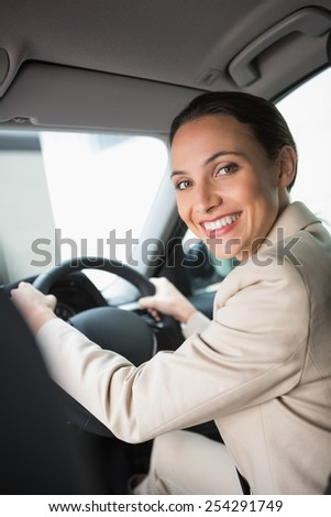 Pretty businesswoman smiling and driving in her car - stock photo