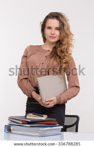 Pretty businesswoman standing in the office near her table. Beautiful lady in business suit looking at the camera isolated on white.