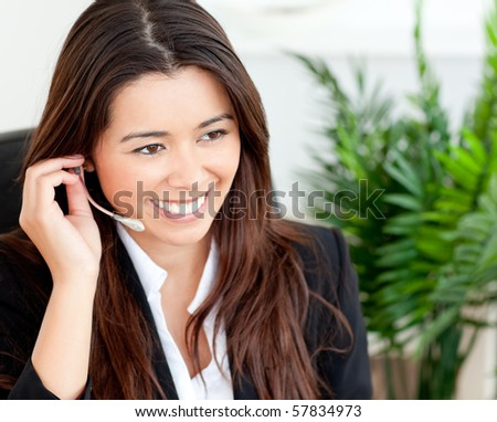 Pretty businesswoman using headset in office - stock photo
