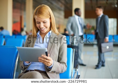 Pretty businesswoman using touchpad while sitting at the airport - stock photo