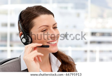 Pretty businesswoman with earpiece sitting in her office