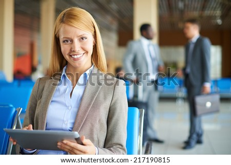 Pretty businesswoman with touchpad looking at camera with two men interacting on background at the airport - stock photo