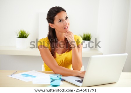 Pretty businesswoman wondering while using her laptop in her office - stock photo
