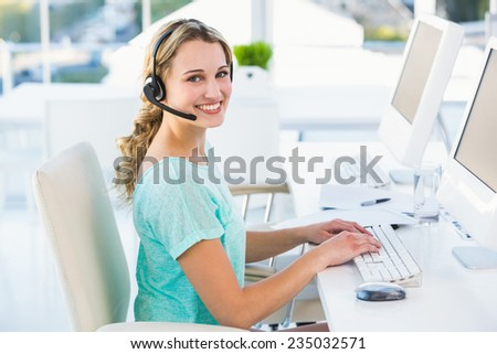Pretty call centre agent sitting at her desk on a call in the office - stock photo