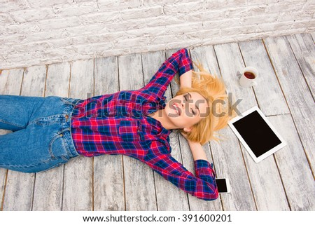 Pretty casual happy girl lying on floor and relaxing - stock photo