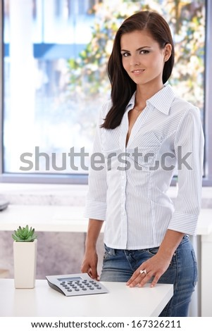 Pretty casual office worker smiling in bright office, standing by desk. - stock photo