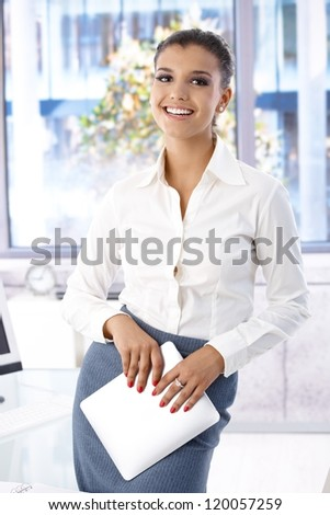 Pretty casual office worker standing in office, smiling.