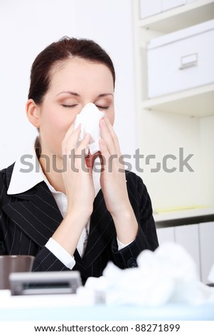 Pretty caucasian businesswoman blowing her nose in the office.