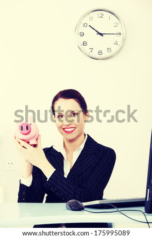 Pretty caucasian businesswoman holding piggy bank in the office. - stock photo