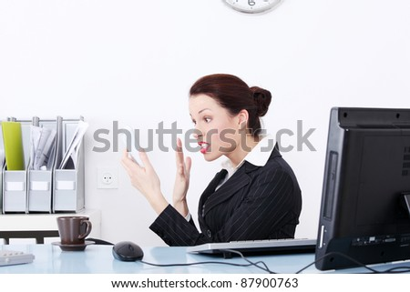 Pretty caucasian businesswoman screaming to phone in the office. - stock photo