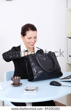 Pretty caucasian businesswoman searching in her black bag at the desk in the office. - stock photo