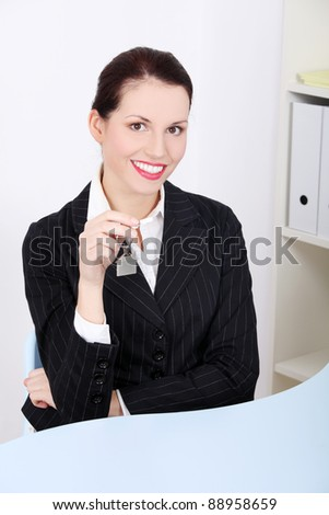 Pretty caucasian businesswoman sitting in the office holding keys.