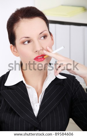 Pretty caucasian businesswoman smoking a electronic cigarette in the office.