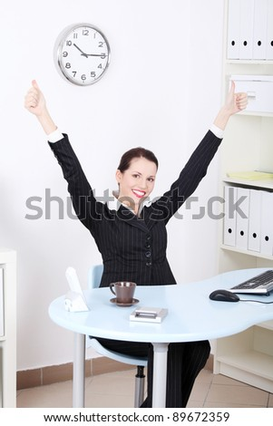 Pretty caucasian businesswoman with hands in the air gesturing okay sign and sitting behind the desk in the office. - stock photo