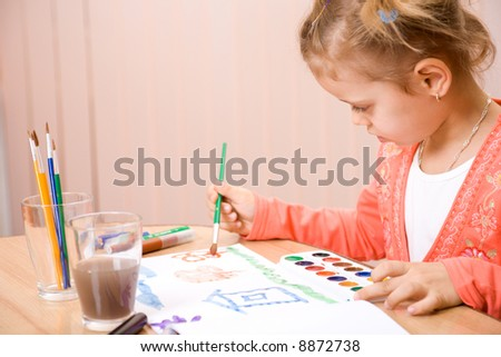Pretty caucasian child watercolor paint . Close-up