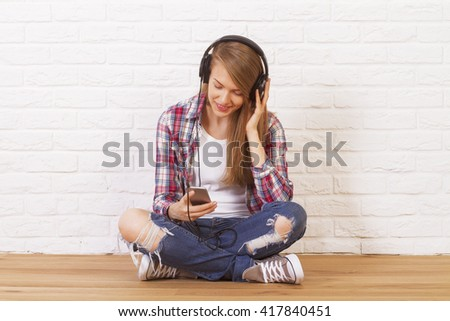 Pretty caucasian female sitting on wooden floor in studio and listening to music. White brick wall background - stock photo