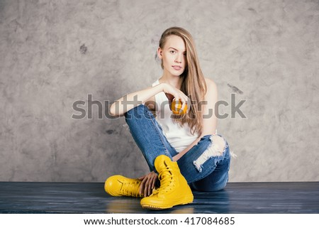 Pretty caucasian girl in yellow boots and with orange in hand sitting on wooden surface on concrete wall background - stock photo