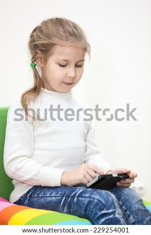 Pretty Caucasian girl playing game on the cellphone, sitting indoor - stock photo