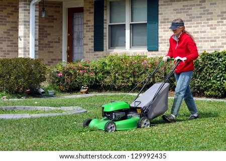 Pretty Caucasian Lady Mowing Her Lawn - stock photo