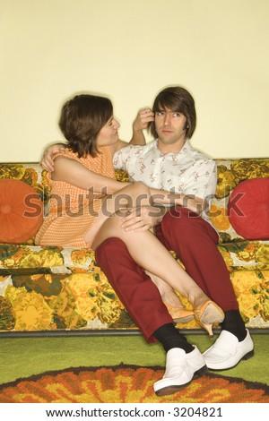 Pretty Caucasian mid-adult woman flirting with Caucasian mid-adult man sitting on colorful retro sofa. - stock photo