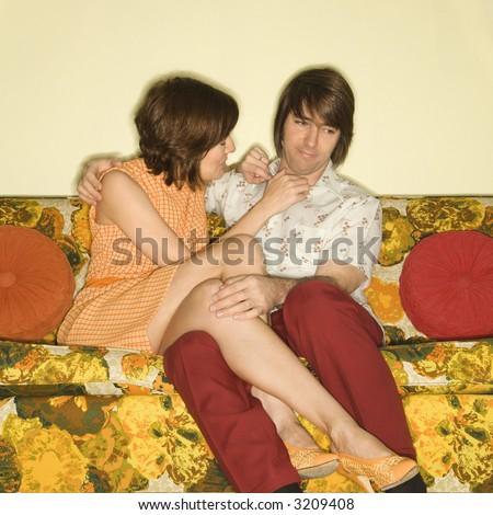 Pretty Caucasian mid-adult woman flirting with shy Caucasian mid-adult man sitting on colorful retro sofa. - stock photo