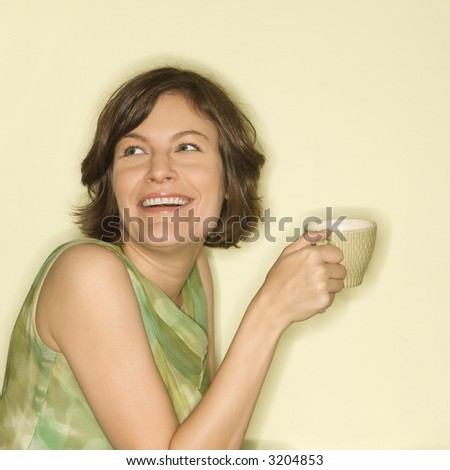 Pretty Caucasian mid-adult woman holding up coffee cup and smiling. - stock photo