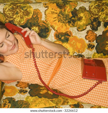 Pretty Caucasian mid-adult woman lying on colorful retro sofa talking on red telephone. - stock photo