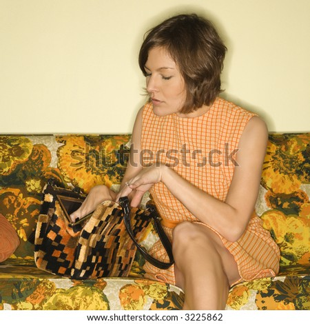Pretty Caucasian mid-adult woman sitting on colorful retro sofa searching in handbag. - stock photo