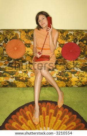 Pretty Caucasian mid-adult woman sitting on colorful retro sofa talking on red telephone. - stock photo