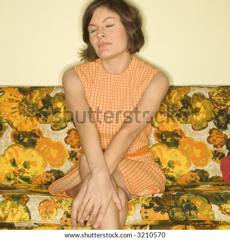 Pretty Caucasian mid-adult woman sitting on colorful retro sofa with arms crossed and eyes closed. - stock photo