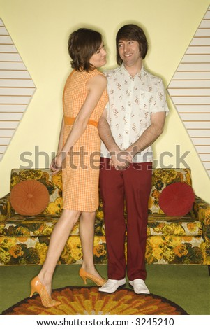 Pretty Caucasian mid-adult woman standing and flirting with shy Caucasian mid-adult man in vintage clothing. - stock photo