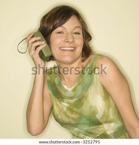 Pretty Caucasian mid-adult woman wearing green vintage dress holding handheld radio up to her ear and smiling at viewer. - stock photo