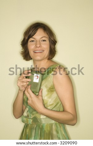 Pretty Caucasian mid-adult woman wearing green vintage dress holding up handheld radio for viewer to see. - stock photo